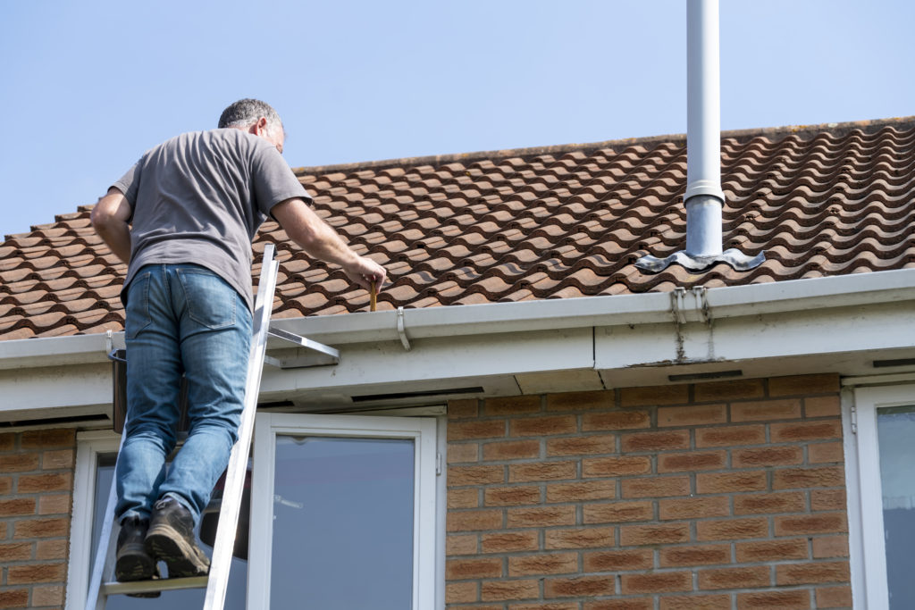 Man performing roof maintenance on his home.